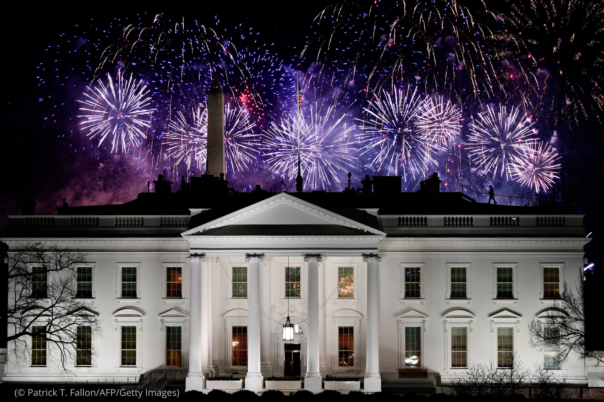 Illuminated White House with Washington Monument and fireworks in background (© Patrick T. Fallon/AFP/Getty Images)