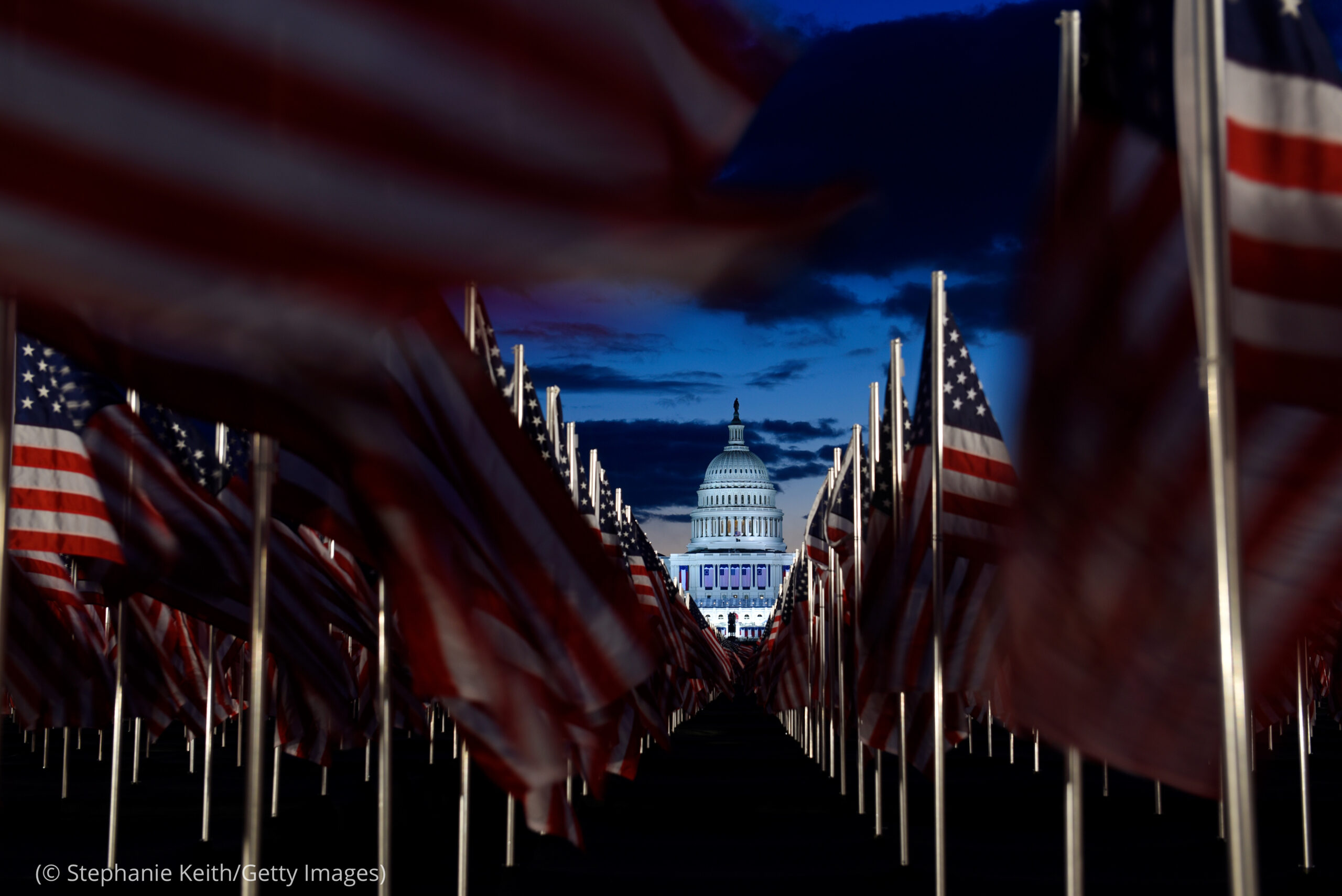 U.S. Capitol building seen at sunrise through rows of U.S. flags stuck in ground (© Stephanie Keith/Getty Images)