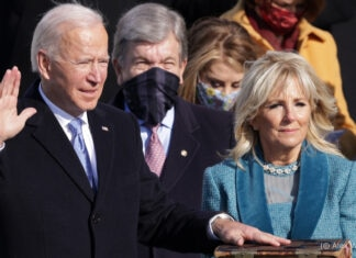 Joe Biden holding one hand up and one hand on Bible held by Jill Biden (© Alex Wong/Getty Images)