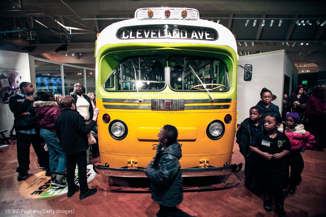 Autobús amarillo y blanco en un museo, con niños alrededor (© Bill Pugliano/Getty Images)