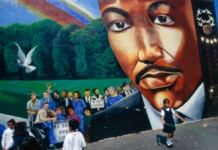 Anak-anak bermain di samping mural yang menggambarkan Martin Luther King Jr. (© David Butow/Corbis/Getty Images)
