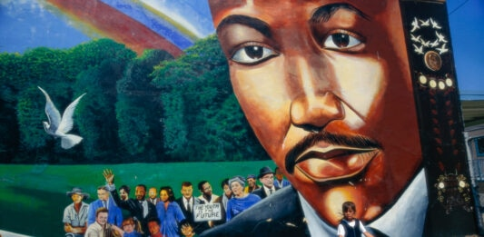 Children playing next to mural depicting Martin Luther King Jr. (© David Butow/Corbis/Getty Images)