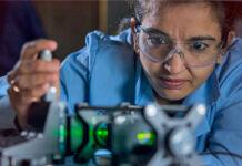 Perempuan mengenakan kacamata pelindung mengamati peralatan (Los Alamos National Laboratory)
