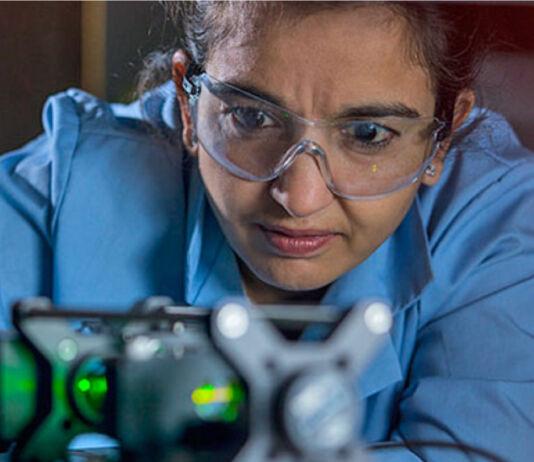 Mulher usando óculos de segurança enquanto olha para equipamento (Cortesia: Laboratório Nacional de Los Alamos)