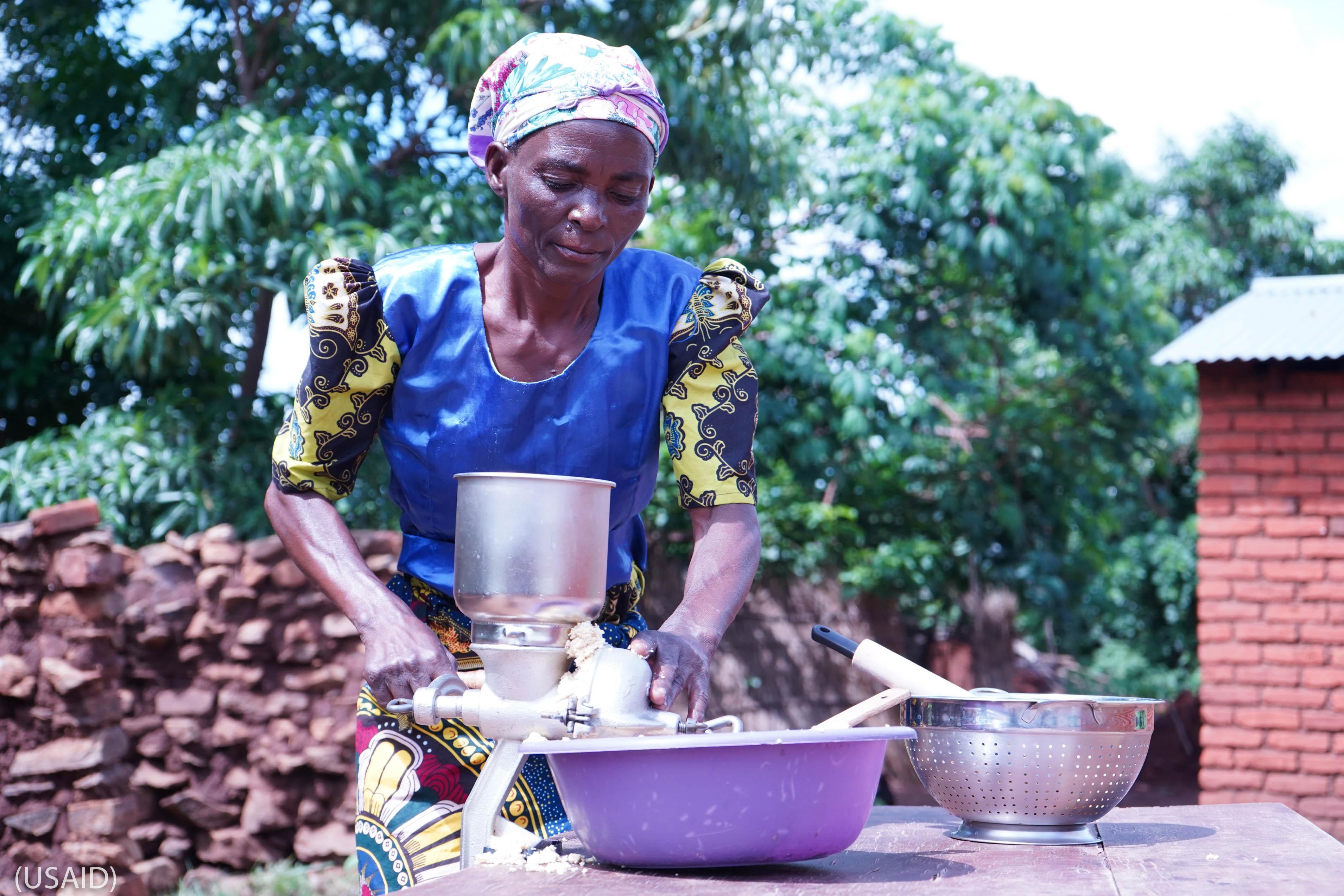 Une femme en train d'utiliser un moulin à main au-dessus d'une cuvette (USAID)