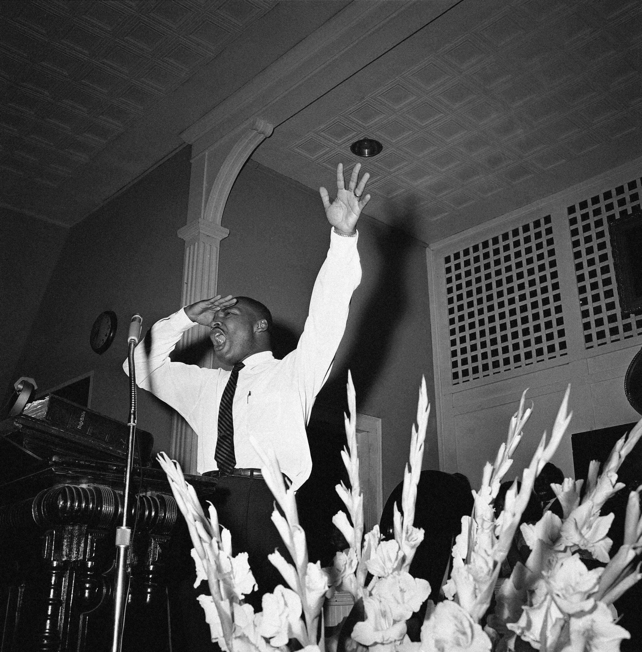 মঞ্চে কথা বলার সময় নাটকীয় ভঙ্গি করছেন মার্টিন লুথার কিং (© এপি ইমেজেস)