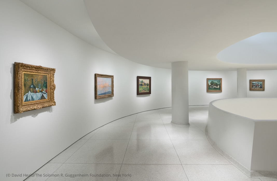 Curved walkway with paintings hanging on wall (© David Heald/Solomon R. Guggenheim Foundation)