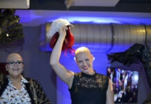 Women with hair loss due to chemotherapy saluting at a fashion show (© Joseph Prezioso/AFP/Getty Images)