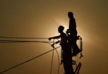 Duas silhuetas de homens em pé no topo de um poste (© Sanjay Kanojia/AFP/Getty Images)