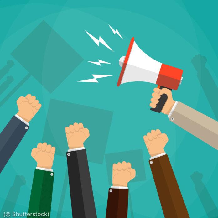 Иллюстрация, на которой изображены поднятые кулаки рядом с рукой с рупором (© Shutterstock)