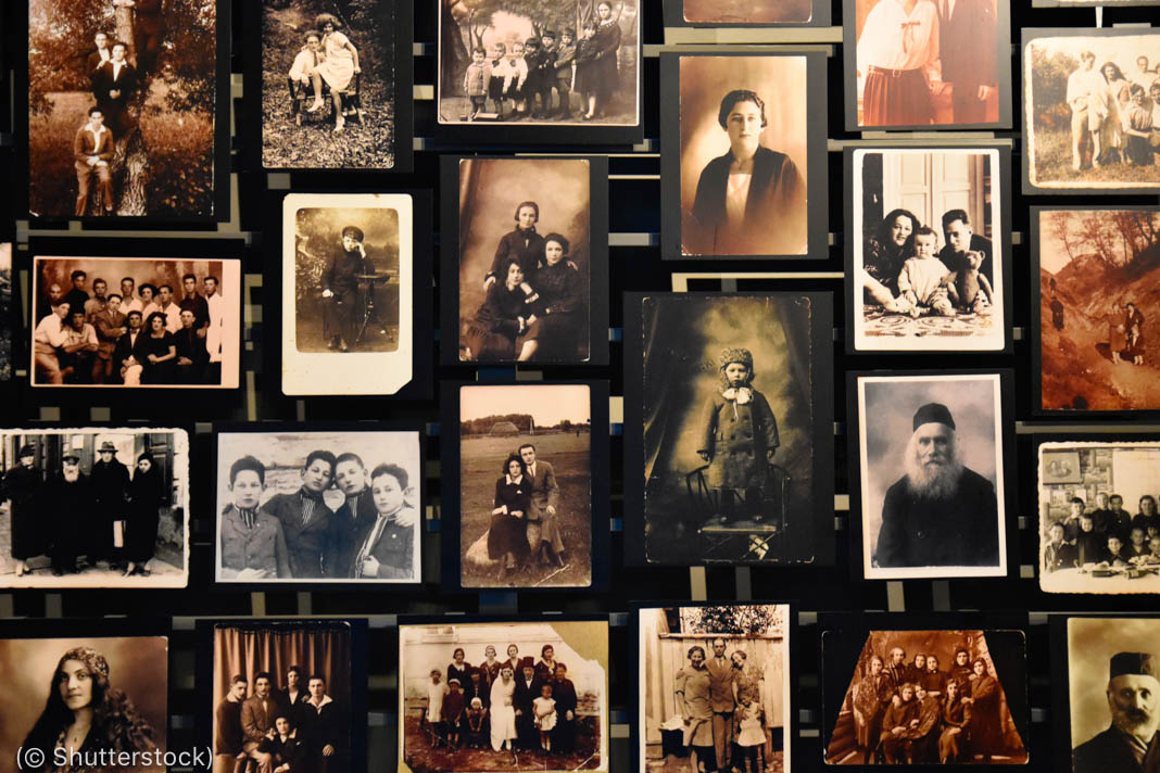 Pictures on a wall of people killed in the Holocaust (© Shutterstock)