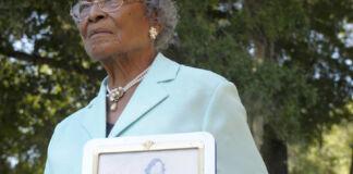 泰勒90岁时在佛罗里达的家前手捧自己的照片(照片:美联社)