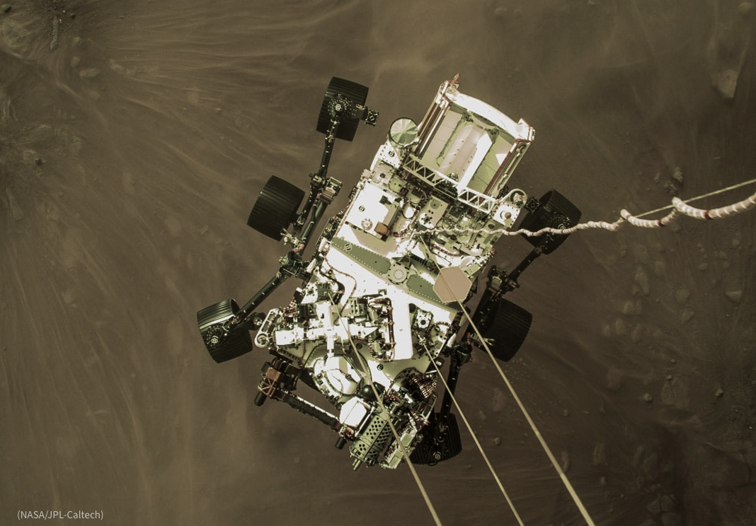 Rectangular device with six wide wheels and multiple instruments being lowered by cables onto barren surface (NASA/JPL-Caltech)