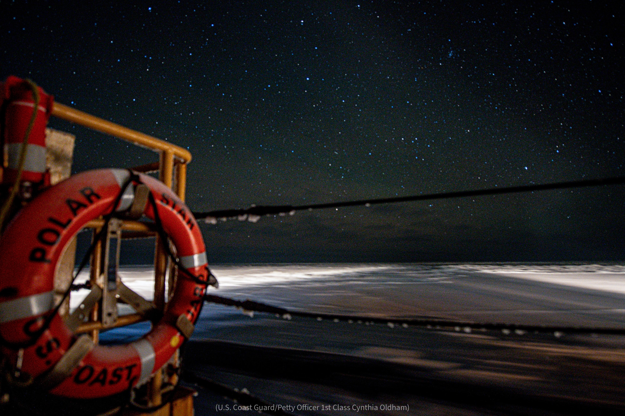 View past ship's buoy of snowy open water and starry night sky (U.S. Coast Guard/Petty Officer 1st Class Cynthia Oldham)