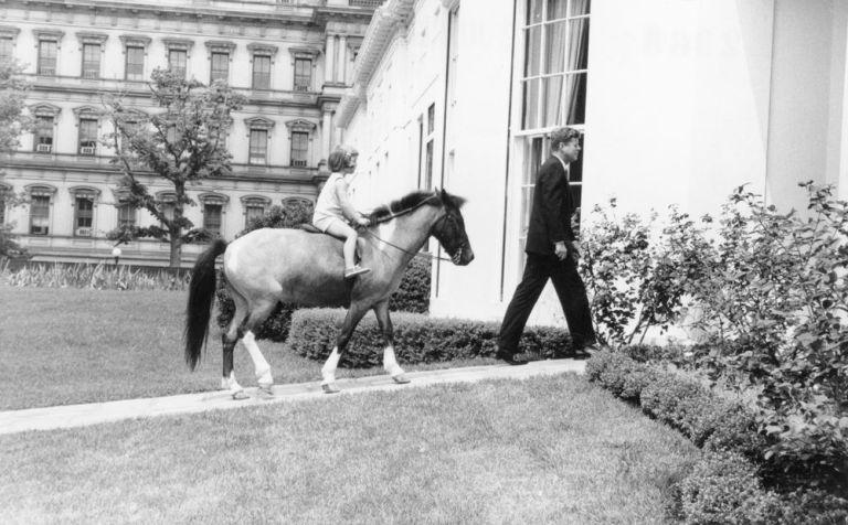这是在1962年6月22日,肯尼迪总统从南草坪走去椭圆形办公室。 他的女儿卡洛琳·肯尼迪骑着小马跟在后面。(国家档案馆博客网站)