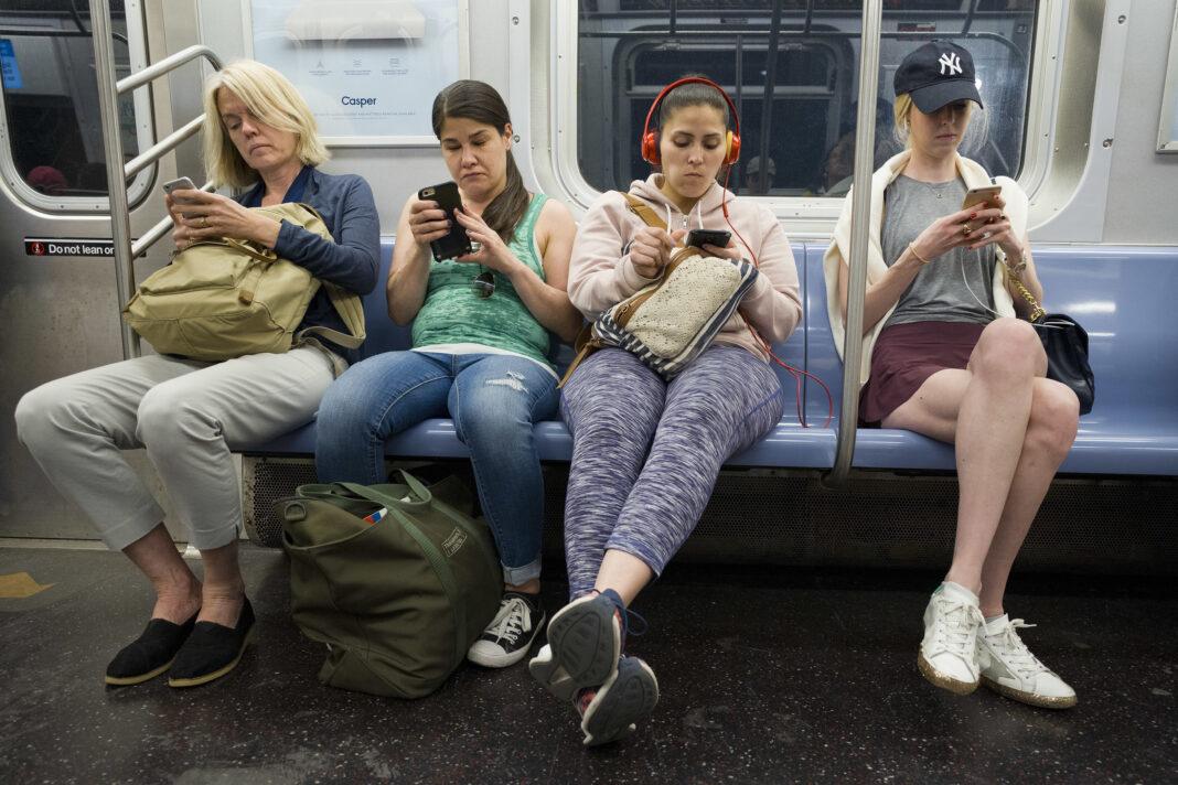 纽约市地铁上的乘客正在看手机(照片:美联社)