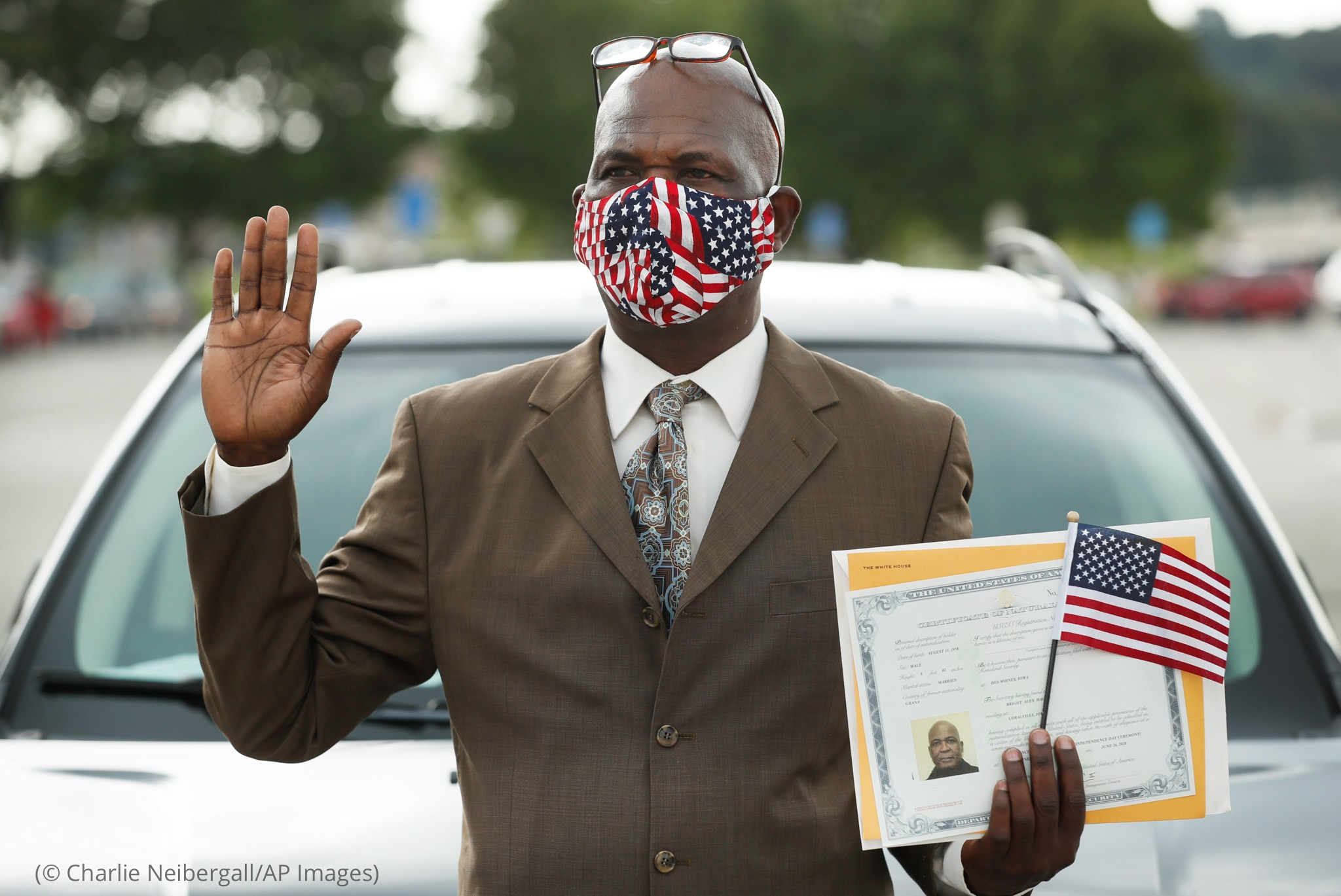 Man with right hand raised and other holding certificate and small flag (© Charlie Neibergall/AP Images)