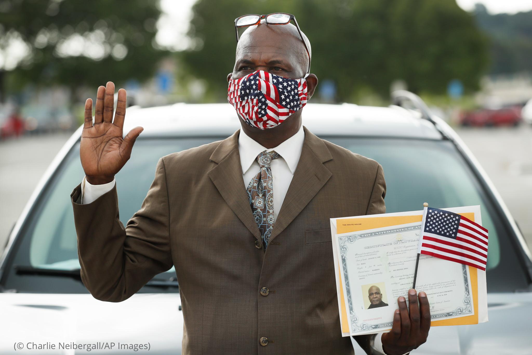 ایک آدمی جس نے دایاں ہاتھ ہوا میں بلند کیا ہوا ہے اور دوسرے ہاتھ میں سرٹیفکیٹ اور چھوٹا جھنڈا پکڑا ہوا ہے (© Charlie Neibergall/AP Images)
