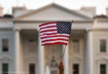 হোয়াইট হাউজের সামনে হাতে ধরা যুক্তরাষ্ট্রের পতাকা (© ক্যারোলিন কাস্টার/এপি ইমেজেস)