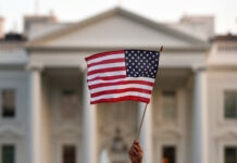 Hand holding U.S. flag in front of White House (© Carolyn Kaster/AP Images)