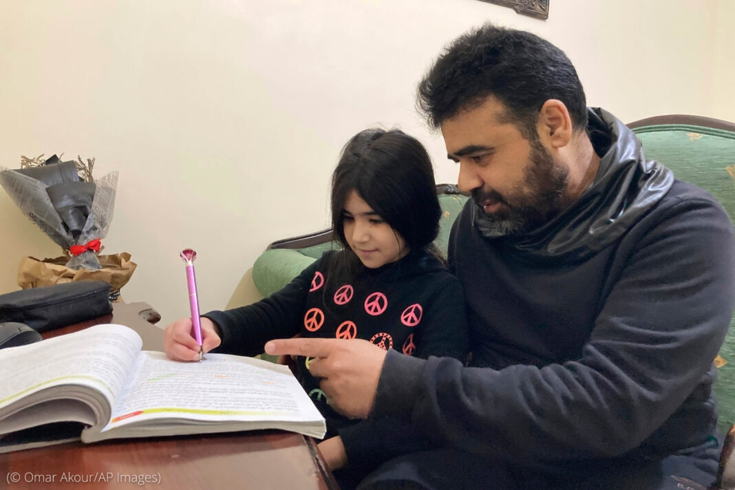 Man sitting with little girl working on homework (© Omar