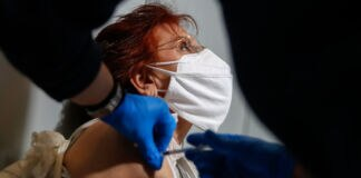Woman in mask receiving vaccination (© Thanassis Stavrakis/AP Images)