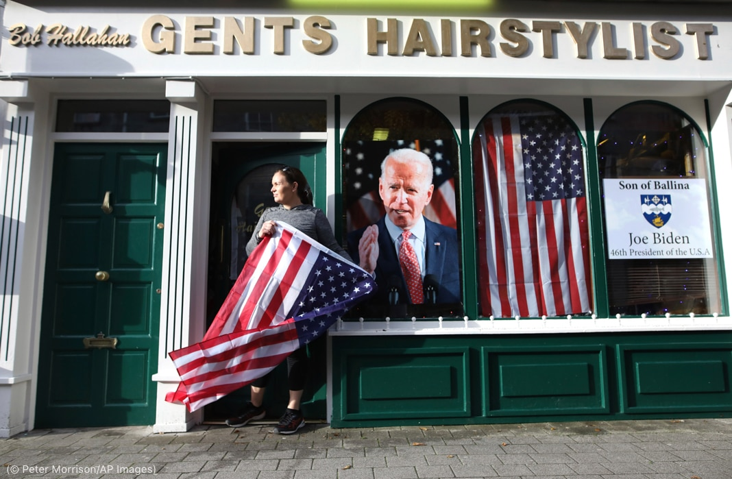 Woman holding U.S. flag in front of shop with Joe Biden photo and U.S. flag in windows (© Peter Morrison/AP Images)
