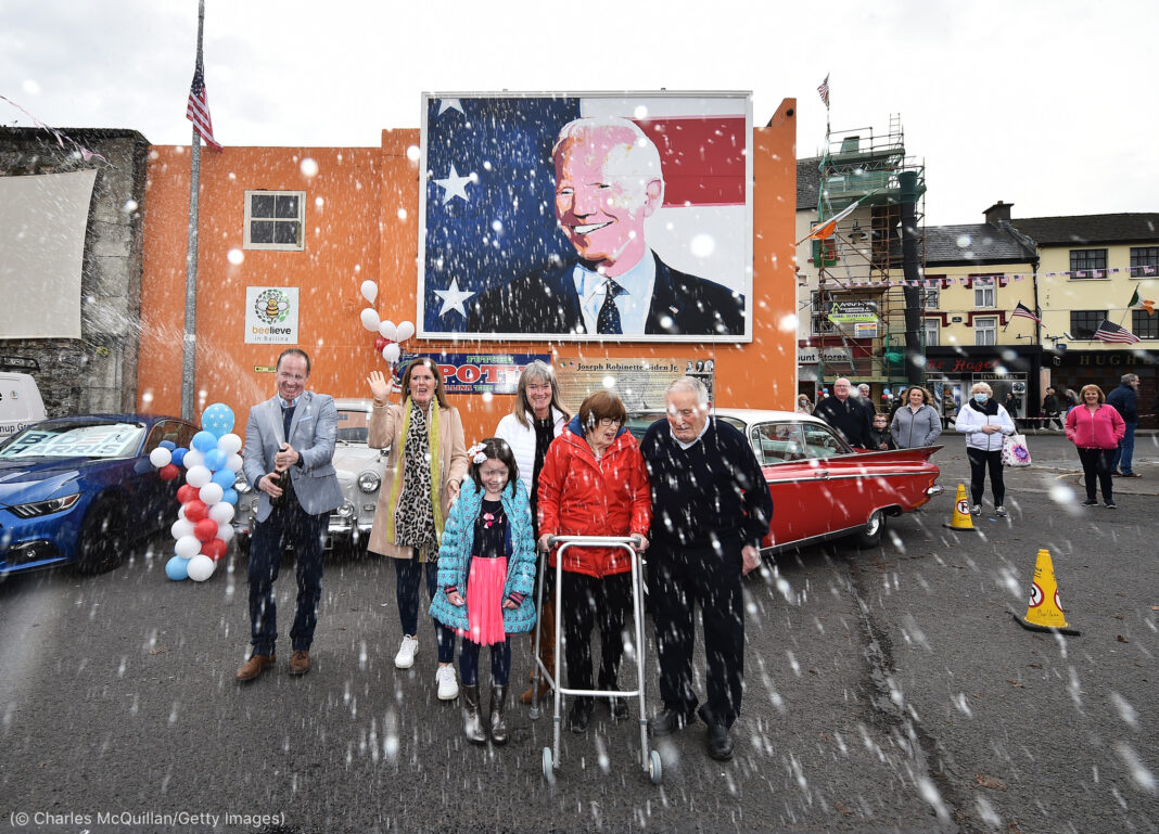 Man spraying bottle of champagne next to a group of people in an Irish town with a Joe Biden mural in the background (© Charles McQuillan/Getty Images)