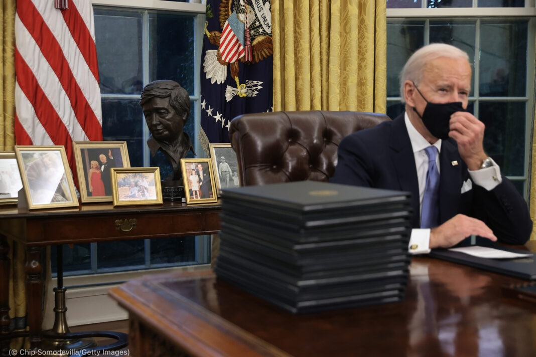President Joe Biden touching his face mask in the oval office with Cesar Chavez bust and framed photos on a table behind him (© Chip Somodevilla/Getty Images)