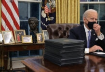 President Biden touching his mask while sitting at desk with César Chávez bust and framed photos on table behind him (© Chip Somodevilla/Getty Images)