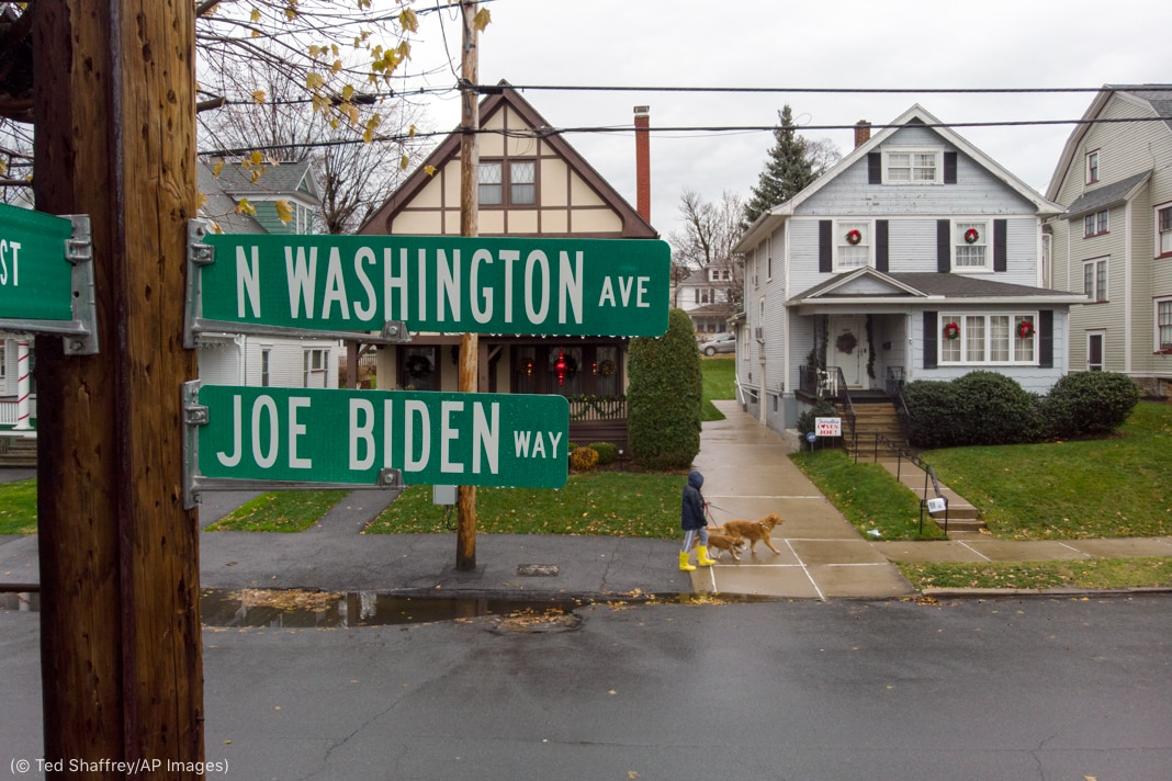 Joe Biden Way road sign attached to wooden pole next to street (© Ted Shaffrey/AP Images)