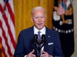 Joe Biden speaking into microphones (© Patrick Semansky/AP Images)