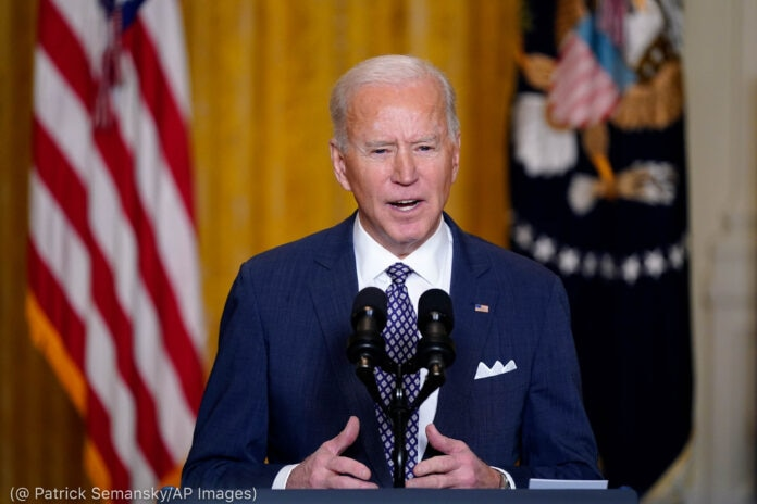 President Joe Biden speaking into microphones (© Patrick Semansky/AP Images)