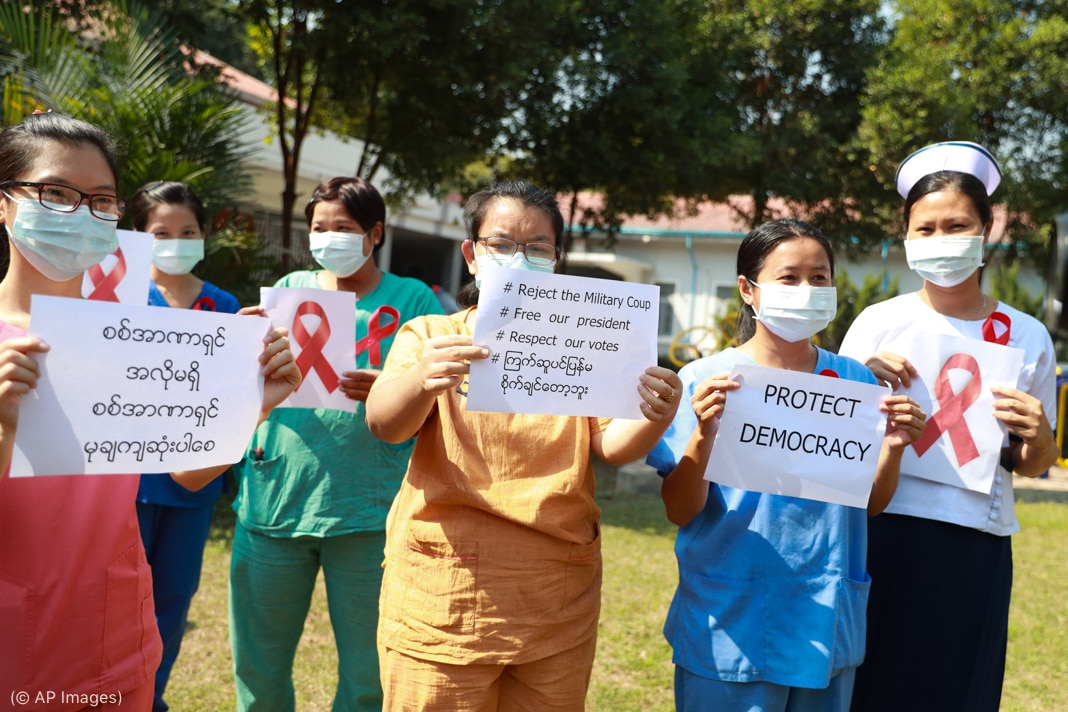 Women in scrubs and face masks holding signs about protecting democracy (© AP Images)