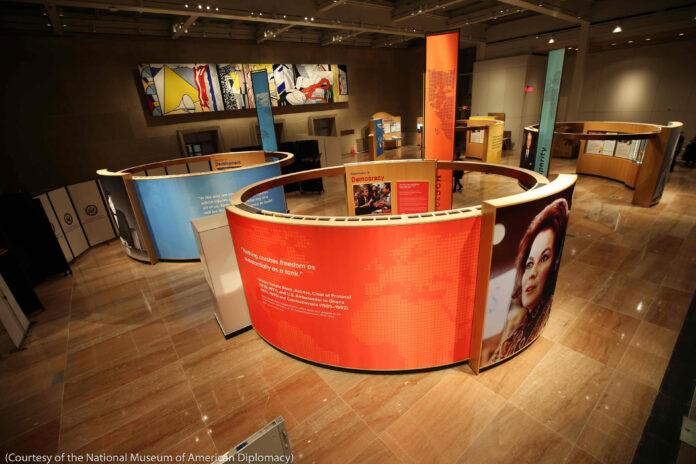 Une exposition dans une salle, avec des photos et du texte affichés sur des panneaux circulaires (avec l'aimable autorisation du Musée national de la diplomatie américaine)