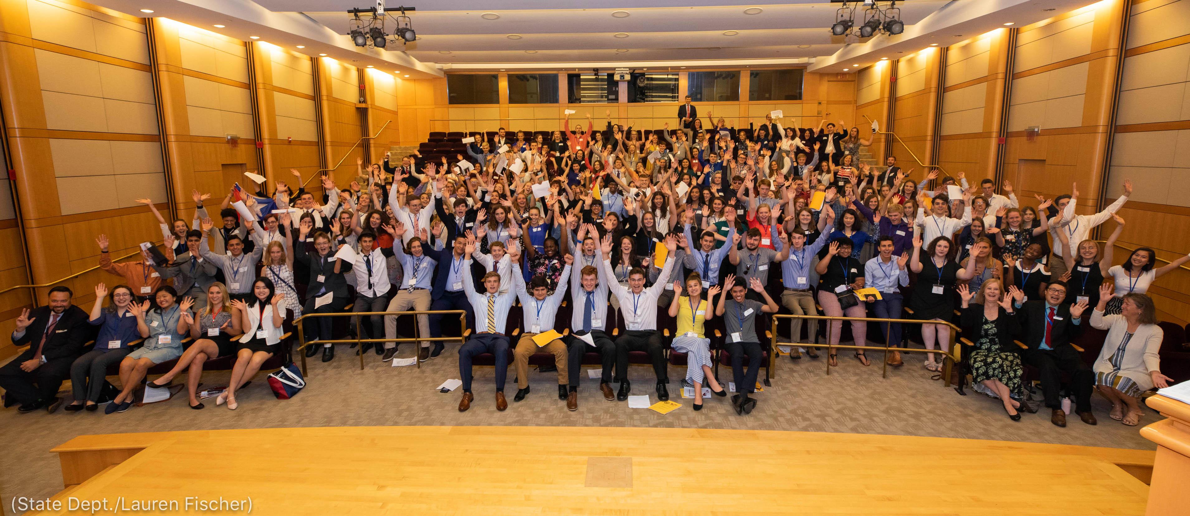 Des personnes assises dans une salle, levant les bras (Département d'État/Lauren Fischer)