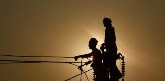বিদ্যুতের খুঁটির উপর দাঁড়ানো দুইজন ব্যক্তির প্রতিচ্ছায়া (© সঞ্জয় কানোজিয়া/এএফপি/গেটি ইমেজেস)