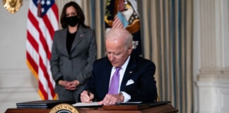 President Biden signing papers with Vice President Harris looking on (© Doug Mills/The New York Times/Getty Images)
