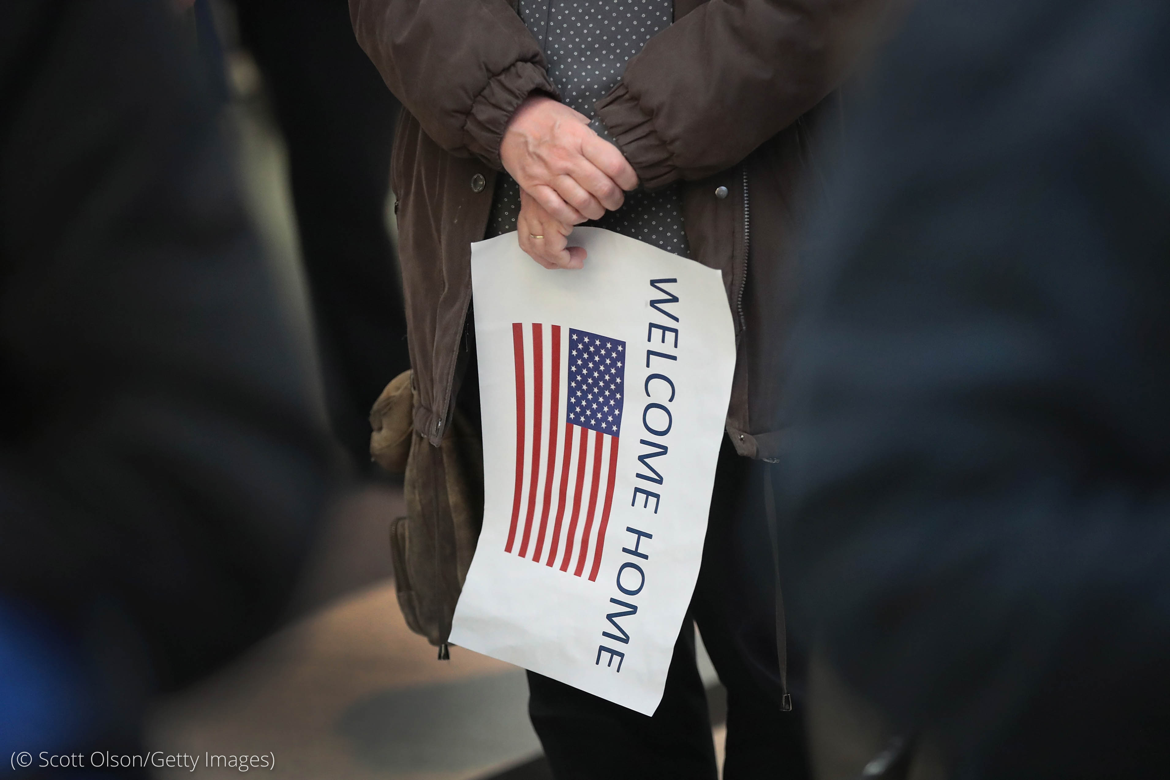 "Person holding ""Welcome Home"" sign with American flag illustration on it (© Scott Olson/Getty Images)"