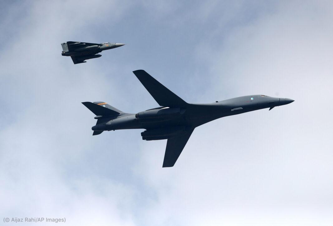 Un bombardier dans le ciel, et un plus petit avion en vol au-dessus du bombardier et à l'arrière (© Aijaz Rahi/AP Images)