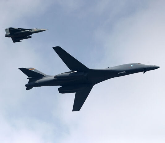 Large bomber flying with smaller combat aircraft (© Aijaz Rahi/AP Images)