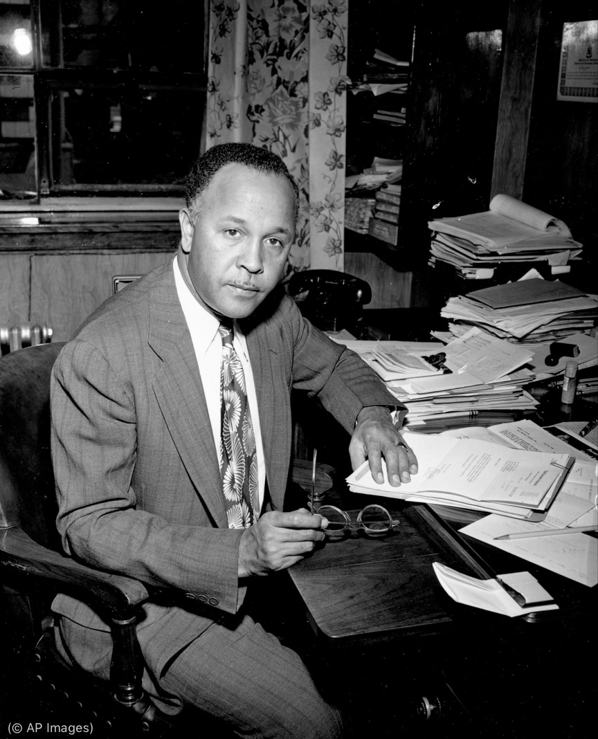 Percy Julian sitting in chair in office (© AP Images)