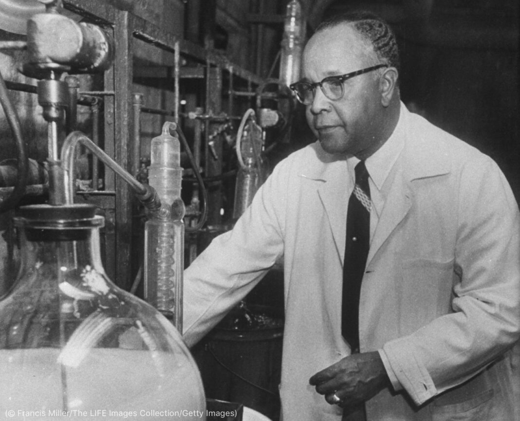 Percy Julian wearing white coat while standing in lab (© Francis Miller/The LIFE Picture Collection/Getty Images)