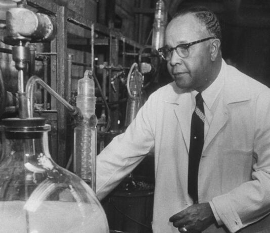 Percy Julian mengenakan jas putih sambil berdiri di sebuah lab (© Francis Miller / The LIFE Picture Collection / Getty Images)