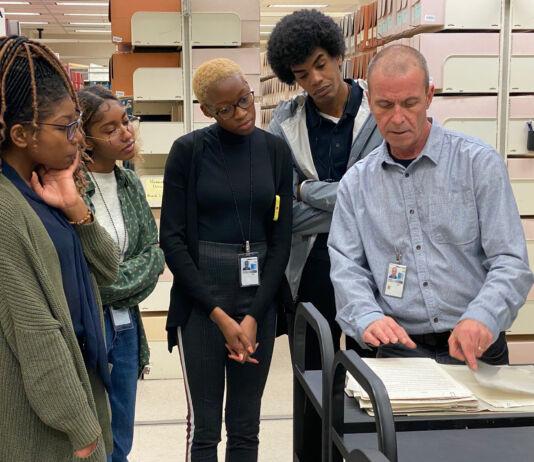 Personas reunidas alrededor de un hombre que señala documentos (Biblioteca del Congreso/Kimberly Powell)