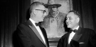 Ralph Bunche holding a medal in his left hand and shaking hands with Oscar Strauss II (© Marty Lederhandler/AP Images)