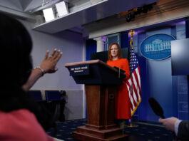 سٹیج پر کھڑیں وائٹ ہاؤس کی پریس سیکرٹری بات کر رہی ہیں اور کرسی پر بیٹھی ایک عورت ہاتھ اٹھائے ہوئے ہے (© Alex Brandon/AP Images)