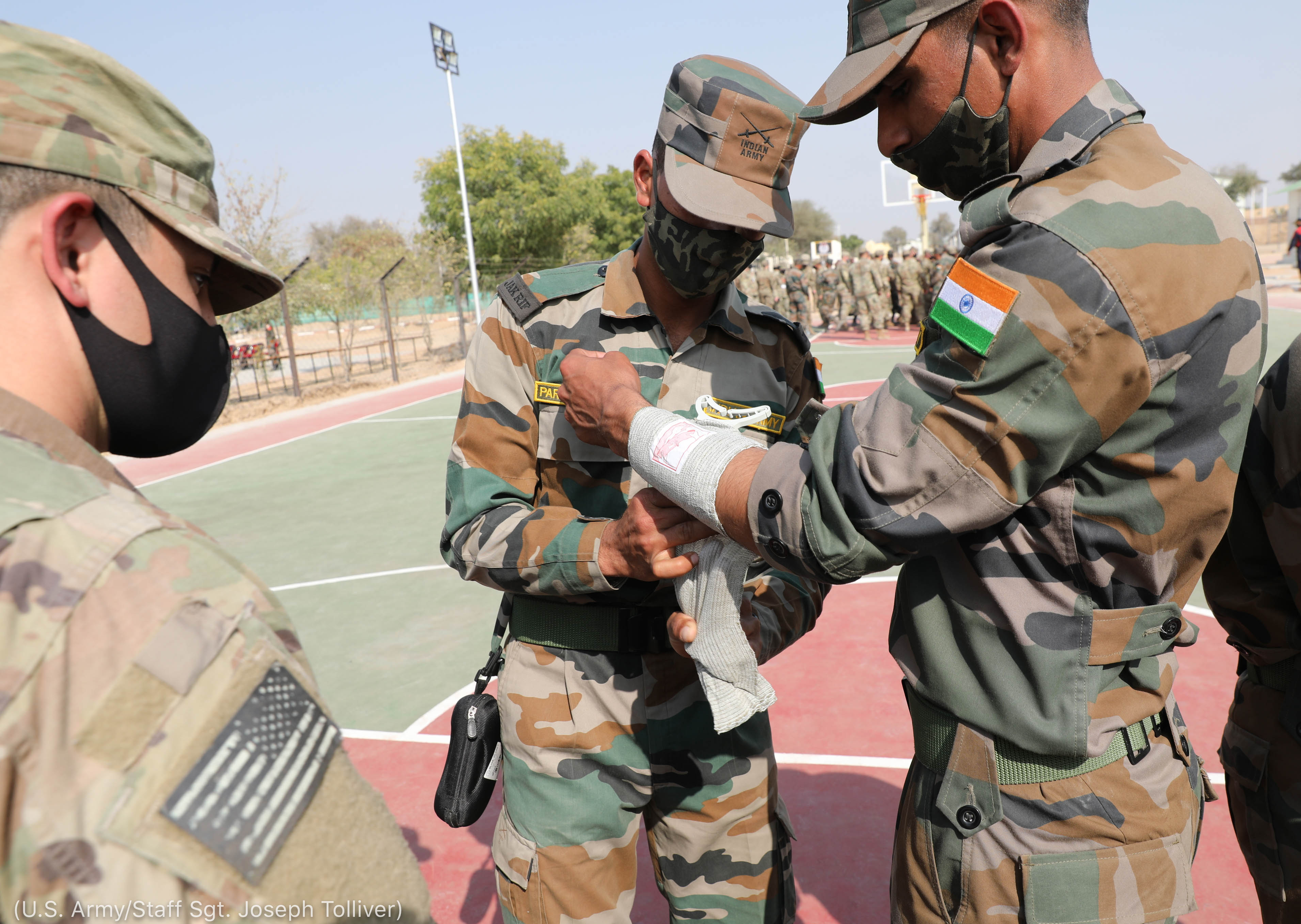 People in Indian and U.S. military uniforms wrapping bandages around arms (U.S. Army/Staff Sgt. Joseph Tolliver)