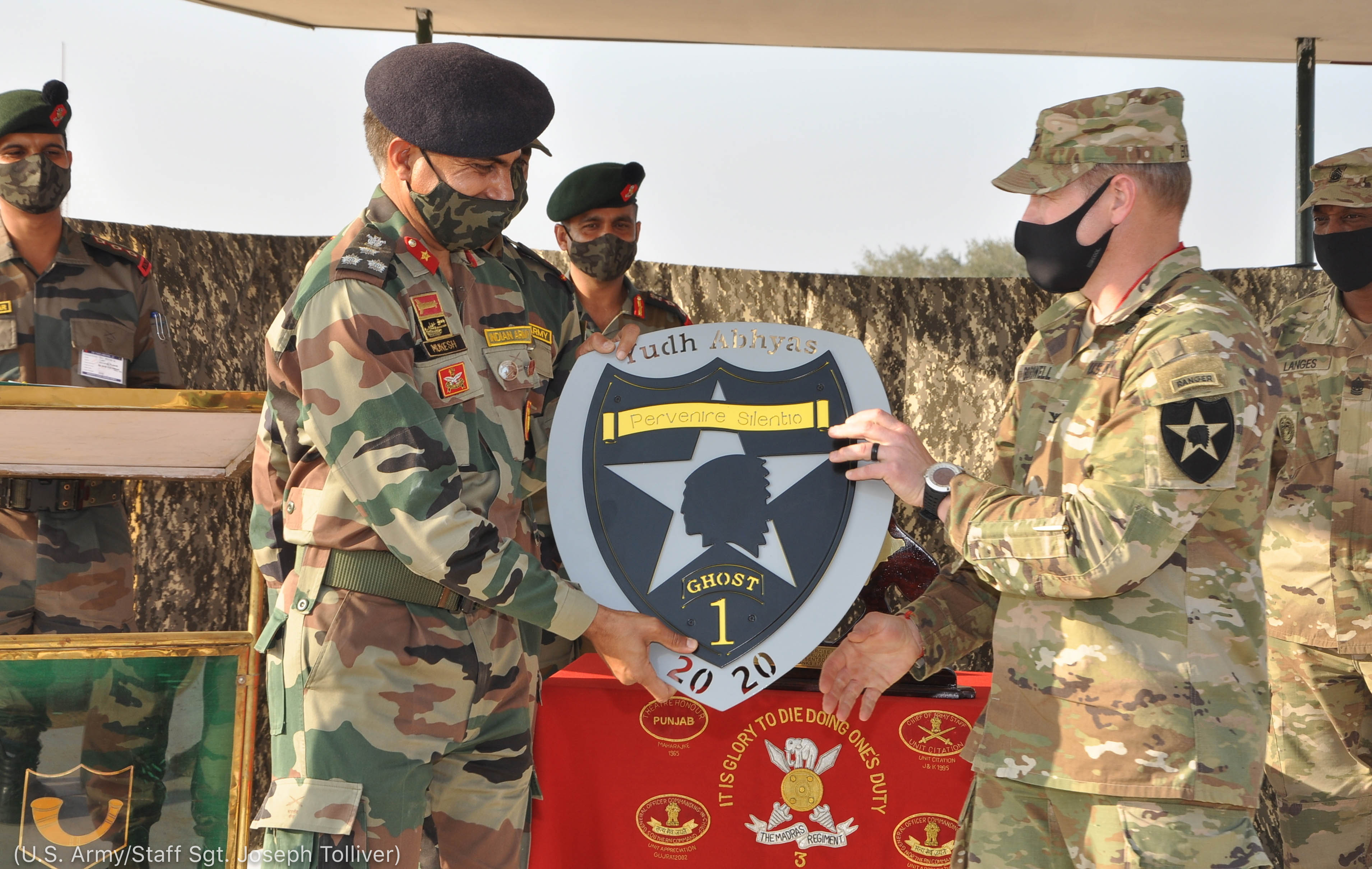 Two people in military uniforms holding a Yudh Abhyas plaque between them (U.S. Army/Staff Sgt. Joseph Tolliver)