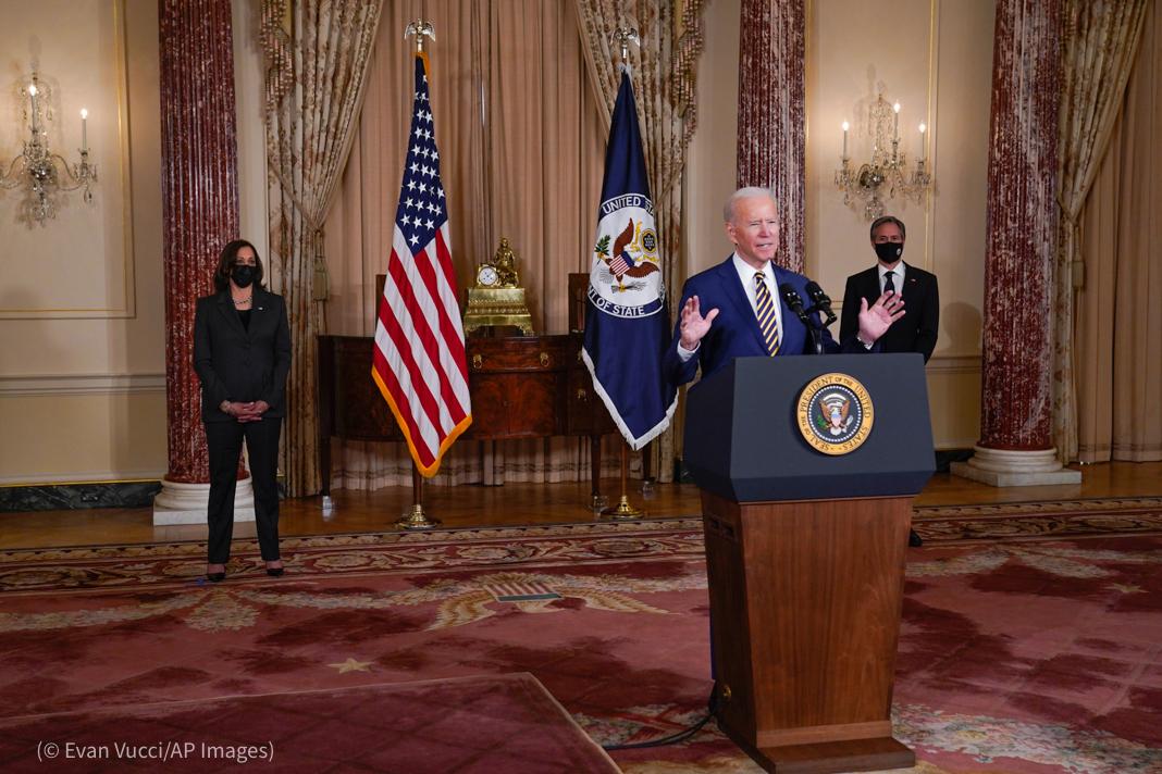 Joe Biden at lectern with Kamala Harris and Antony Blinken standing behind him by flags (© Evan Vucci/AP Images)